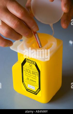 Ein Einweg-Injektionsnadel in einem klinischen Abfallbehälter entsorgen - Stockfoto
