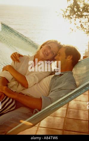 Junges Paar teilen Hängematte auf der Terrasse am Meer. - Stockfoto