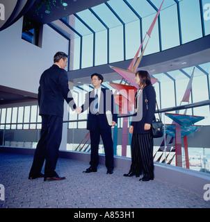 Zwei Männer und Frau stehend indoor Hochparterre modernen Geschäftshauses. Handshake-Gruß. - Stockfoto