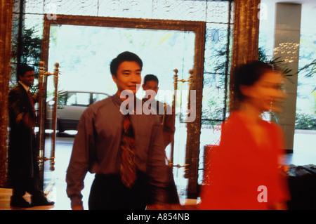 Junges Paar Ankunft im Hotel wird vom Portier im Foyer begrüßt. - Stockfoto