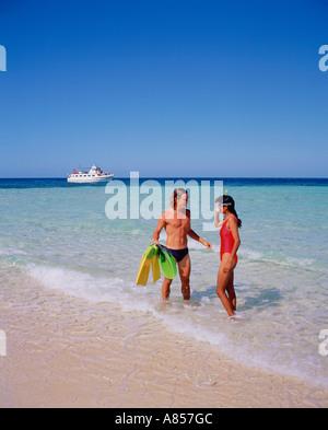 Zwei junge Menschen in Badeanzügen stehend an einem Strand mit Dive Boot im Hintergrund. Australien. Queensland. - Stockfoto