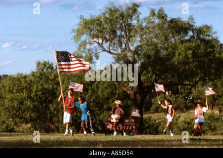 Kinder spielen im Park am 4. Juli mit Flaggen - Stockfoto