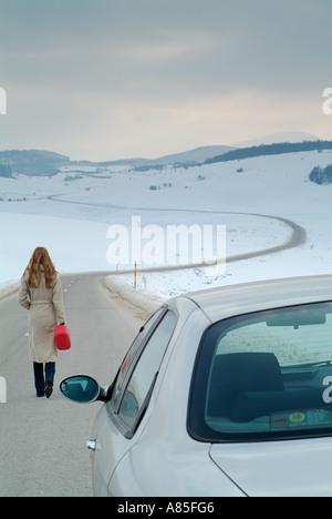Frau beginnt den langen Weg auf einer abgelegenen Landstraße im Winter, Kraftstoff für ihr Auto kaputt zu finden - Stockfoto