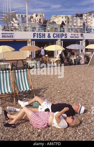 Brighton Seafront ein älteres Ehepaar genießen Sie Sommersonne liegend auf dem Kiesstrand Sussex HOMER SYKES - Stockfoto