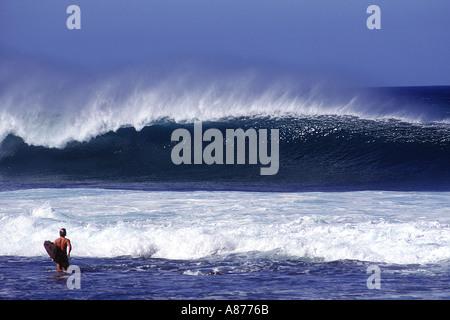 Eine tolle Welle stürzt wie ein Surfer hält eine Surf Board Spaziergänge in die glänzende blaue Wasser - Stockfoto