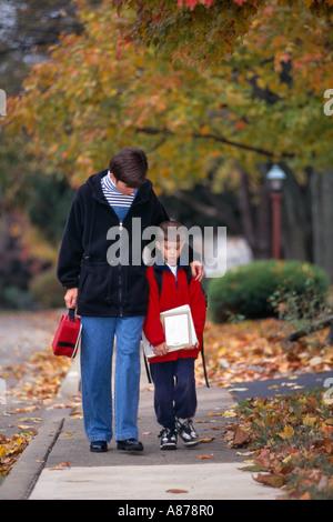 Mutter zu Fuß Sohn von der Schule nach Hause nach einem harten Tag in der Schule - Stockfoto