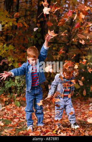 Zwei junge Brüder spielen im Herbst Laub und Blätter in die Luft werfen - Stockfoto