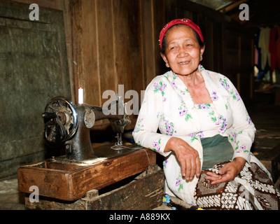 Lächelnde Frau lehnt sich auf ihrer Nähmaschine in Markthalle, Madiun, Java, Indonesien - Stockfoto