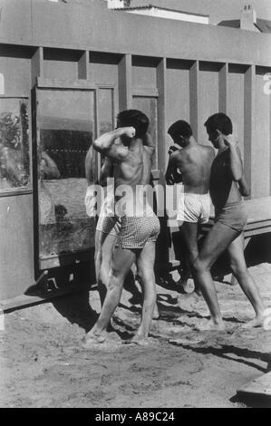 Drei Jungs im Teenageralter ihre Muskeln und posiert vor dem Spiegel im Freien am Strand wurde in den 1950 s Bild - Stockfoto