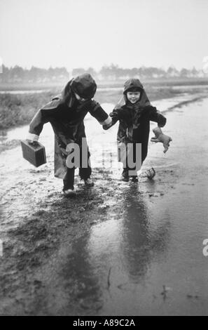 Zwei junge Brüder tragen dunkle Regen Slickers in Pfützen springen, während gemeinsam zur Schule gehen - Stockfoto