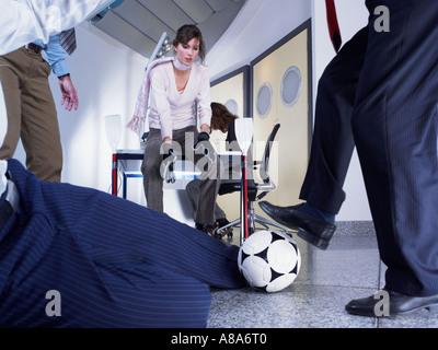 Büroangestellte, die Fußball spielen - Stockfoto