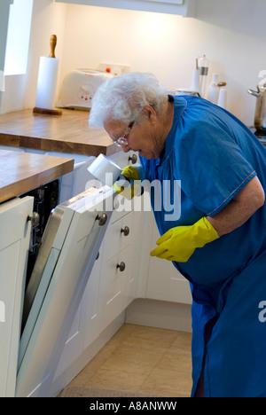 Unabhängige ältere Dame, die Lupe mit Sehbehinderung verwendet und die Anweisungen für den feinen Druck auf ihrem - Stockfoto