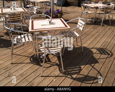 Chrom und Holz Café Stühle und Tisch in der Sonne wirft einen Schatten auf Boden Belag - Stockfoto