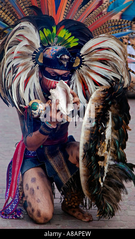 Eine AZTEKISCHE Tänzer bläst eine Muschel in einer traditionellen gefiederten Krieger Kostüm während des CERVANTINO - Stockfoto