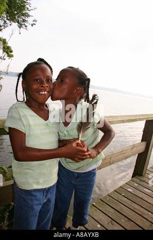 Zwei Afro amerikanische Mädchen umarmen und küssen auf dem Dock in der Nähe von See. - Stockfoto