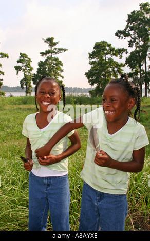 Zwei Afro amerikanische jungen Mädchen spielen zusammen im Park. - Stockfoto