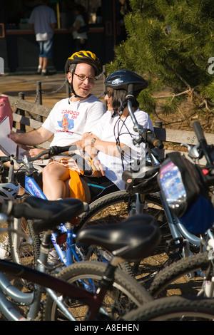 CHICAGO Illinois erwachsenes paar einen Fahrradhelm tragen sitzen auf Bank neben geparkten Fahrrädern Lincoln Park - Stockfoto