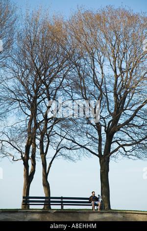 CHICAGO Illinois Mann sitzen auf der Parkbank zwischen Bäumen Lake Michigan See - Stockfoto