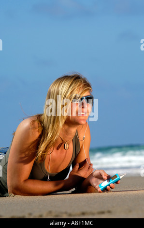 eine Fit gesunde junge Frau, die entspannende Musik auf iPod am Sandstrand - Stockfoto