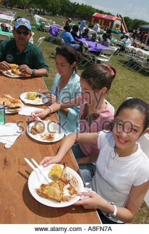 Miami Florida Tropical Park DFYIT Familie Picknick spanischer Familie Esstisch Papptellern essen - Stockfoto