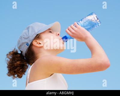 Teenager-Mädchen tragen leichte blaue Kappe trinken Mineralwasser gegen blauen Himmel-Seitenansicht - Stockfoto