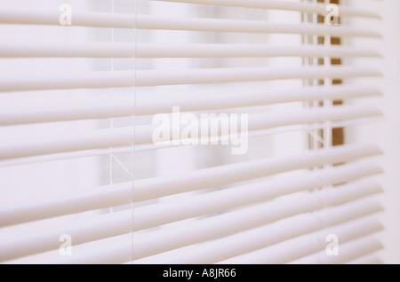 Impressionistische Detail der weiße Jalousien nach unten aber offen mit einer Lamelle mit Blick auf weiße Gebäude - Stockfoto