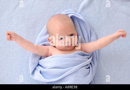 Neugeborenes Baby mit ausgestreckten Armen auf blaue Decke - Stockfoto