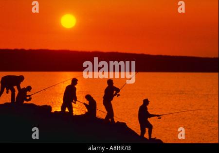 Silhouette der Fischer bei Sonnenuntergang - Stockfoto