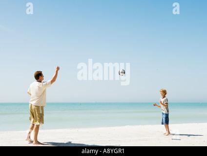 Vater und Sohn wirft Ball am Strand - Stockfoto