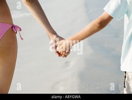 Kind, Hand in Hand mit älteren Schwester am Strand, Nahaufnahme - Stockfoto