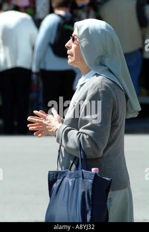 Nonne in Blau gekleidet und trägt eine Einkaufstasche zu beten.  Pisa-Toskana-Italien-EU-EU - Stockfoto