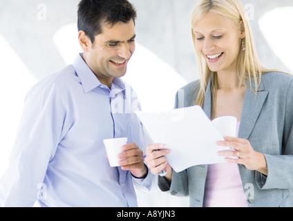 Geschäftspartnern Kaffeetrinken und das Dokument lesen und lachen - Stockfoto