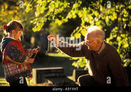 Großvater spielen Conkers mit Enkelin - Stockfoto