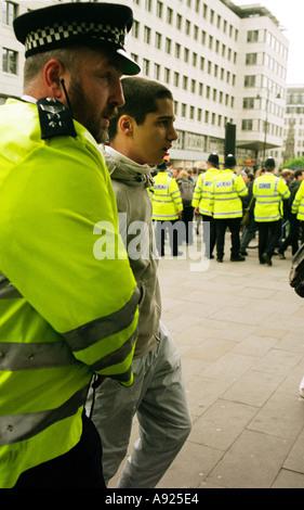 Polizisten verhaften einen jungen Mann an einer Demonstration im Zentrum von London, Mayday 2003. - Stockfoto