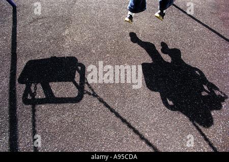 Der Schatten eines jungen Mädchen oder junge spielt auf einer Schaukel