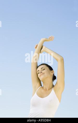 Frau streckte Arme über Kopf, Himmel im Hintergrund, niedrigen Winkel Ansicht Stockfoto