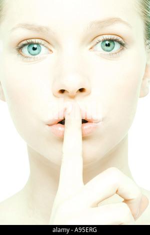 Teenager-Mädchen mit Finger über die Lippen, Nahaufnahme, Vorderansicht - Stockfoto