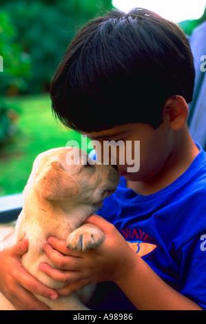 Ein kleiner Junge mit einem kleinen blonden Welpen kuscheln - Stockfoto