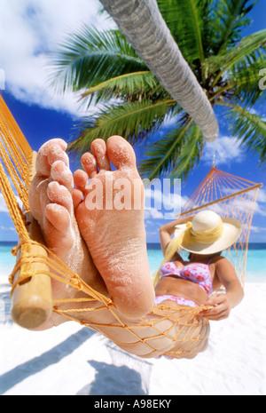 Frau mit sandigen Füßen ruht in der Hängematte unter Strohhut - Stockfoto