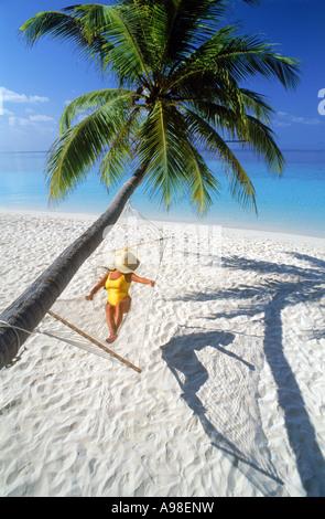 Frau mit Hut und gelben Badeanzug zum Entspannen in der Hängematte unter Palme erstreckt sich über den weißen Sandstrand - Stockfoto