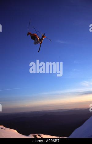 Skifahrer, die hoch in die Luft, als er von einem Felsvorsprung auf brillant klarem Wetter Mt Hood oder springt - Stockfoto