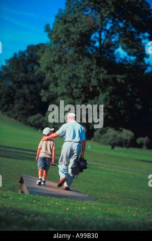 Ein Vater mit seinem Golf-Bag und Clubs hat seinen Arm um seine Schultern Sohn, wie sie über eine Brücke auf einem - Stockfoto