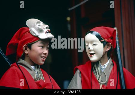 JAPAN Honshu Nikko Herbst Festival zwei jungen in traditioneller Tracht tragen Masken. - Stockfoto