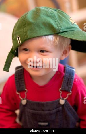 Niedlichen Kleinkind Lachen und tragen Baseball-Kappe seitlich. Lodz Polen - Stockfoto