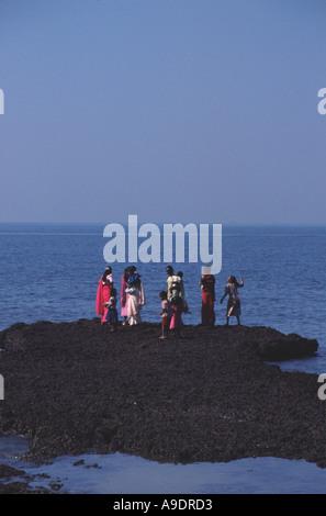 GOA. Frauen auf den Felsen am Anjuna Strand. - Stockfoto