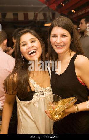 Zwei Mädchen posiert für die Kamera auf eine Nacht in einem belebten Londoner bar - Stockfoto