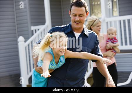 Ein Mann spielt mit seiner Tochter vor Hof - Stockfoto