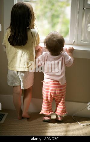 Kleines Mädchen mit langen braunen Haaren stehen mit ihrem Kleinkind Schwester schaut aus dem Fenster - Stockfoto