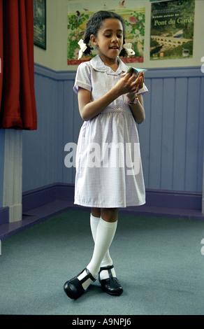 Kleines Schulmädchen mit einem Papier Wahrsagen Spielzeug zu spielen. - Stockfoto