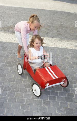 Schwester schob ihre jüngere Schwester in ein Spielzeugauto - Stockfoto